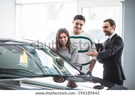 Beautiful young couple choosing a car at the dealership talking to the salon manager with tablet in hands
