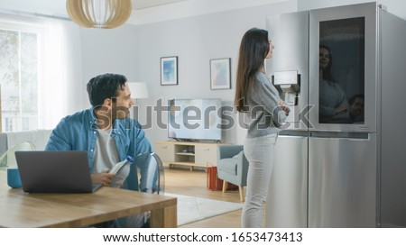 Beautiful Young Couple Drink Morning Coffee in the Kitchen. Girl Checks the Weather Forecast and a To Do List on a Smart Fridge at Home. Apartment is Bright and Cozy.