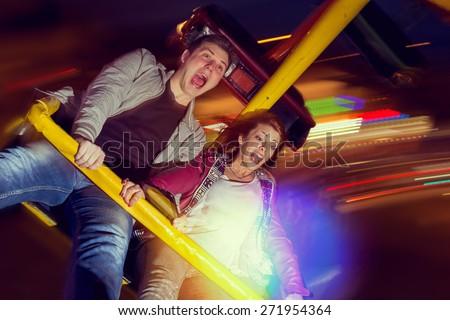 Beautiful, young couple having fun at an amusement park Stock photo ©