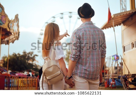 Beautiful, young couple having fun at an amusement park. Couple Dating Relaxation Love Theme Park Concept. Couple posing together on the background of a ferris wheel. Tourists have fun, smile.