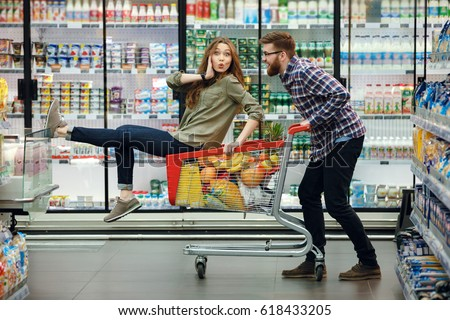 Beautiful young couple having fun while choosing food in the supermarket. Young happy man pushing shopping cart with his girfriend inside