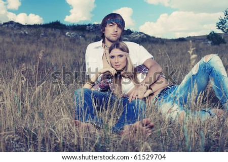 Beautiful young couple hippie posing together over picturesque landscape.