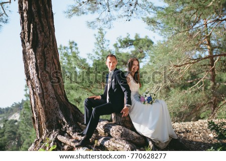 Beautiful young couple honeymooning in the forest hugging and holding hands. The enamored married girl hugs her husband. #770628277