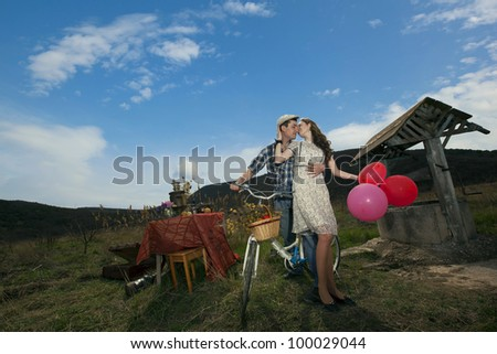beautiful young couple hugging and kissing in a field near the well and set table with bicycle and colored balloons