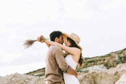 beautiful young couple hugging in sand canyon with cloudy sky