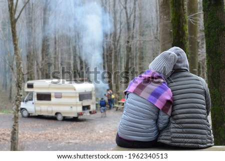Beautiful young couple hugging with love in the camp. Silhouette of loving couple looking caravan camping in autumn holiday, back view. Stok fotoğraf ©