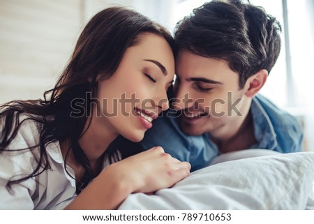 Beautiful young couple in bedroom is lying on bed. Enjoying spending time together.