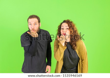 Beautiful young couple in love, kissing, throwing kisses with their hands. Romantic relationship.