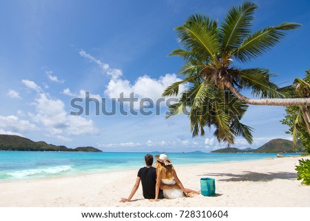 Beautiful young couple in love sitting and relaxing on exotic beach surrounded by palm tree and blue sea from Seychelles Islands. Young couple in honeymoon having holidays on exotic beach #728310604