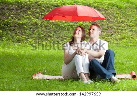 Beautiful young couple in love sitting on green summer meadow under red umbrella