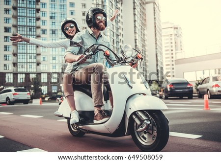 Beautiful young couple in sun glasses and helmets is smiling while riding a scooter #649508059