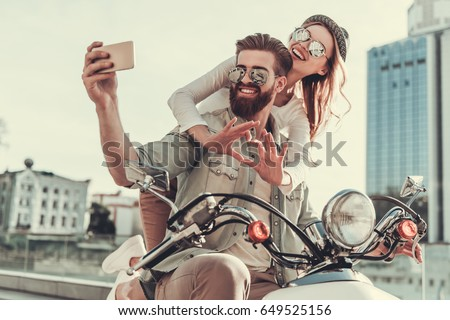 Beautiful young couple in sun glasses is doing selfie using a smart phone and smiling while sitting on a scooter outdoors