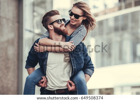 Beautiful young couple in sun glasses looking at each other and smiling while standing outdoors. Girl piggyback
