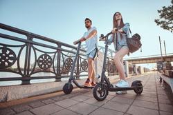 Beautiful young couple is enjoying sunny summer day while riding their own electro scooters.