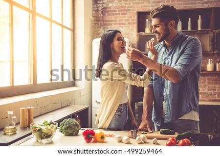 Beautiful young couple is feeding each other and smiling while cooking in kitchen at home #499259464