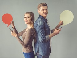Beautiful young couple is holding speech bubbles, using smartphones, looking at camera and smiling while standing back to back on gray background