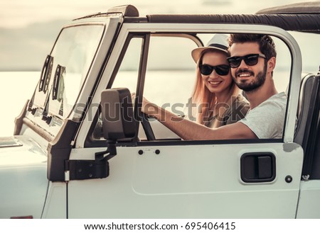 Beautiful young couple is looking at camera and smiling while travelling by car in sunny weather #695406415