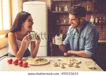 Beautiful young couple is talking, looking at each other and smiling while eating and drinking in kitchen at home #499253653