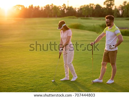 Beautiful young couple is using golf clubs while playing golf together #707444803