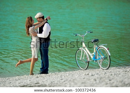 Beautiful young couple kissing and hugging on the coast