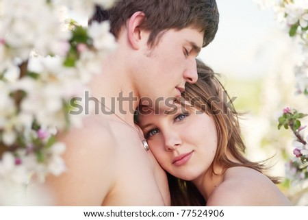 beautiful young couple kissing in the flowering gardens