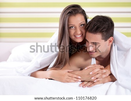 Beautiful young couple lying down under covers in bed, smiling and looking at camera.