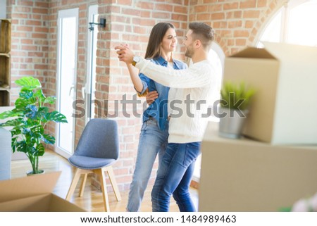 Beautiful young couple moving to a new home, dancing in love celebrating new apartment #1484989463