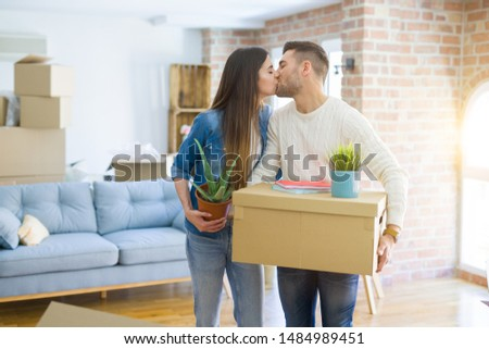 Beautiful young couple moving to a new house, smiling happy holding cardboard boxes at new apartment #1484989451