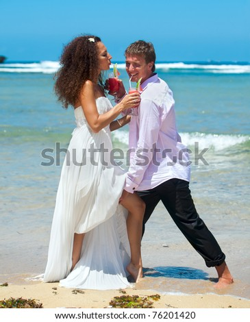 Beautiful young couple on vacation near the ocean with a cocktail in hand