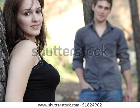 Beautiful young couple outdoors in a park - looking at the camera (focus on the young woman)