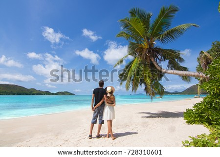 Beautiful young couple relaxing on exotic beach from Seychelles. Lovers under palm tree and surrounded by blue sea from Seychelles Islands. Couple in love travel to exotic destination on honeymoon