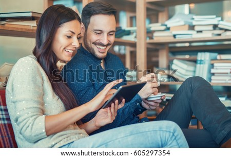 Beautiful young couple sitting in library, surrounded with books on the wooden shelves. Education, dating, university, relationships, lifestyle concept #605297354