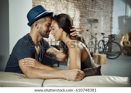Beautiful young couple sitting on sofa, embracing with love, eyes closed. Profile.