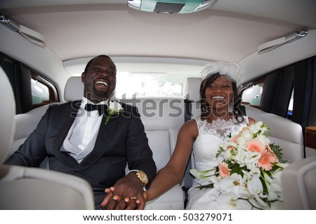 Beautiful young couple smiling happily on wedding-day, sitting in limousine. #503279071