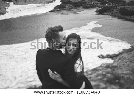 Beautiful young couple standing on a snow in spring mountains. Groom kissing bride. Black and white shot #1100734040