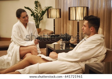 Beautiful young couple wearing toweling robes sitting together at spa  lounge talking enjoying their weekend love 79caa2ff7