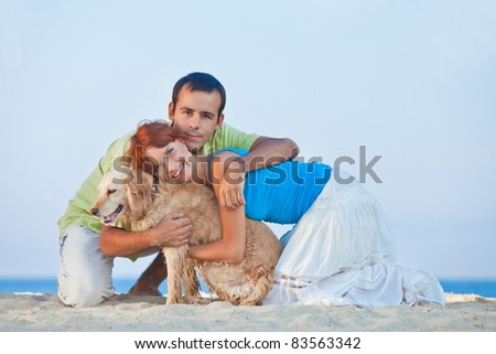 Beautiful young couple with a dog at sea
