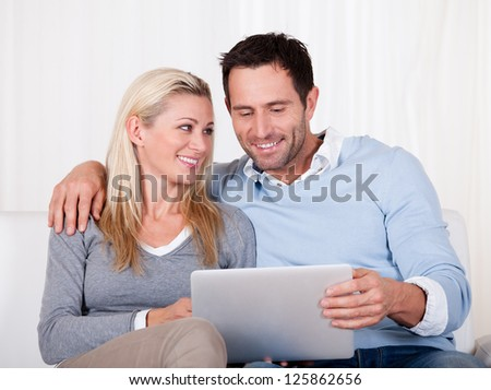 Beautiful young couple with lovely smiles sitting side by side on a sofa looking at a tablet together