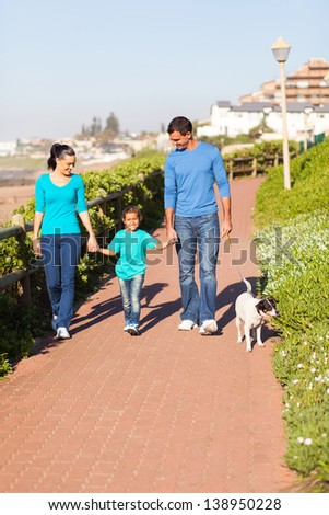 beautiful young couple with their daughter walking pet dog by seaside