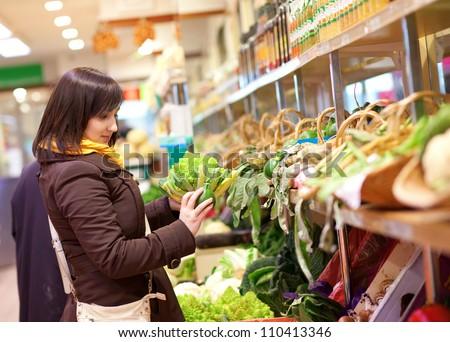 Beautiful young customer buying romanesco broccoli at market