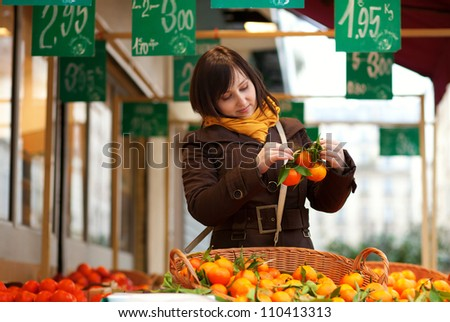Beautiful young customer selecting tangerines at market