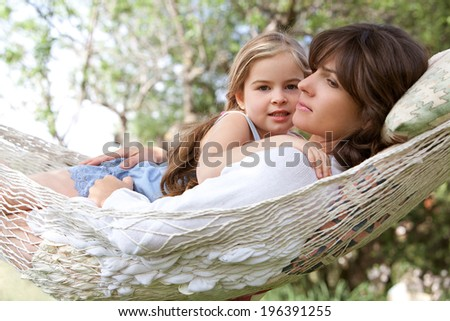 Beautiful young daughter and her mother hugging and enjoying laying together in a hammock during a summer holiday in a home vacation garden during a sunny day. Outdoors healthy  and relaxing lifestyle