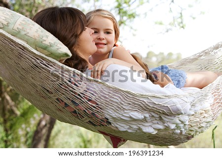 Beautiful young daughter girl and her mother hugging and enjoying laying together in a hammock during a summer holiday in home vacation garden during a sunny day. Outdoors healthy relaxing lifestyle.