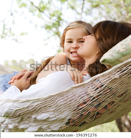 Beautiful young daughter girl and her mother hugging and enjoying laying together in a hammock during a summer holiday in a home vacation garden during a sunny day. Outdoors relaxing lifestyle.