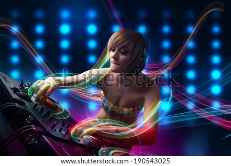 Beautiful young Dj girl mixing records with colorful lights #190543025