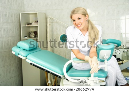 beautiful young doctor sitting on the gynecological chair in her office