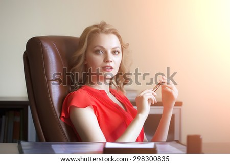 Beautiful young elegant blond business woman sitting in office on brown leather chair in red blouse holding pen in hands looking forward indoor on white background copyspace, horizontal picture