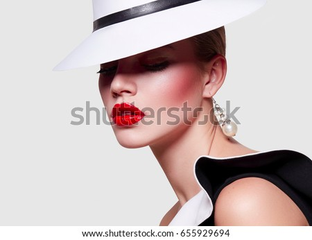 Beautiful young elegant girl in a white gown and a black dress with valans. Portrait on white background. Bright makeup - red lips, arrows in front of eyes. Fashionable attire, gamur, luxury, luxury.