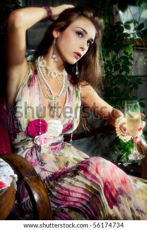 beautiful young elegant  woman drinking champagne in garden