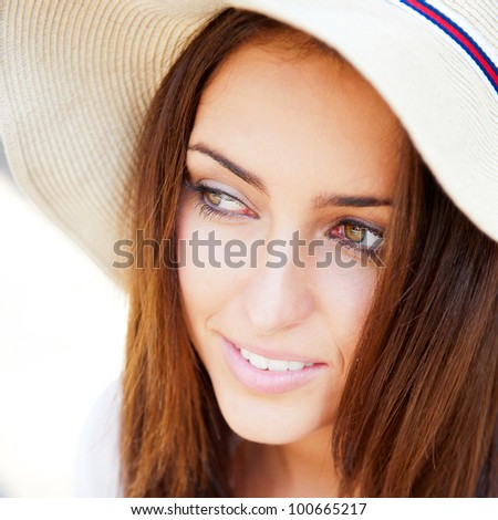 Beautiful young elegant woman wearing hat outdoor at park she is relaxed and daydreaming - stock photo